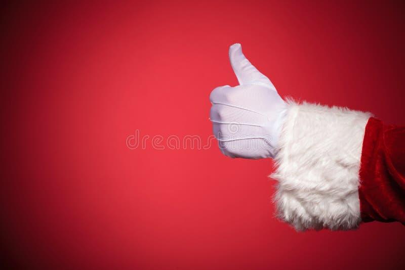 Рука Санта Клауса показывая большие пальцы руки вверх по одобренному знаку стоковое фото rf