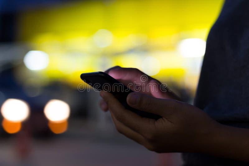 Рука селективного фокуса держа телефон на ноче стоковое изображение rf