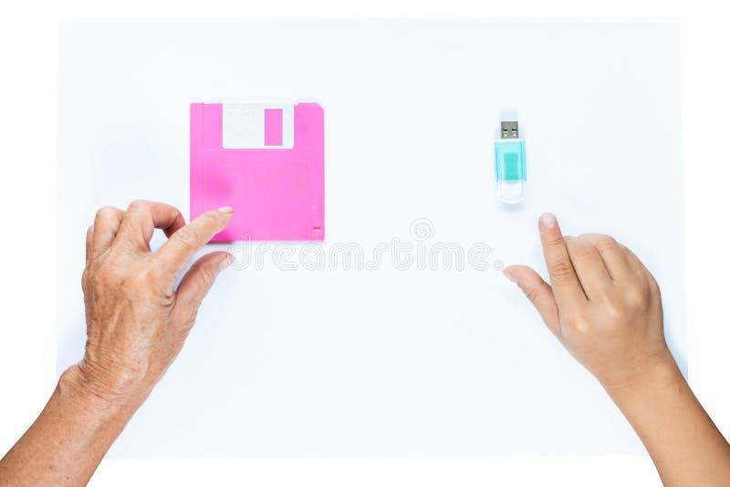 Рука старухи комплектуя вверх дискету и рука маленькой девочки комплектуя вверх внезапную ручку памяти привода, развитие хранения стоковая фотография rf