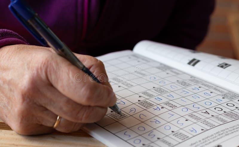 Рука старшего человека делая головоломку кроссвордов в тетради Отдых и свободное время стоковые фотографии rf