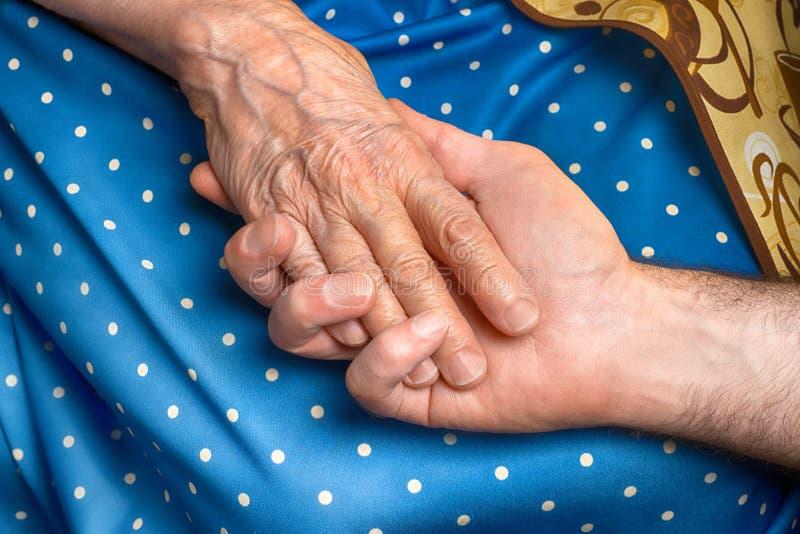 Рука старшей женщины держа руку человека стоковые фотографии rf