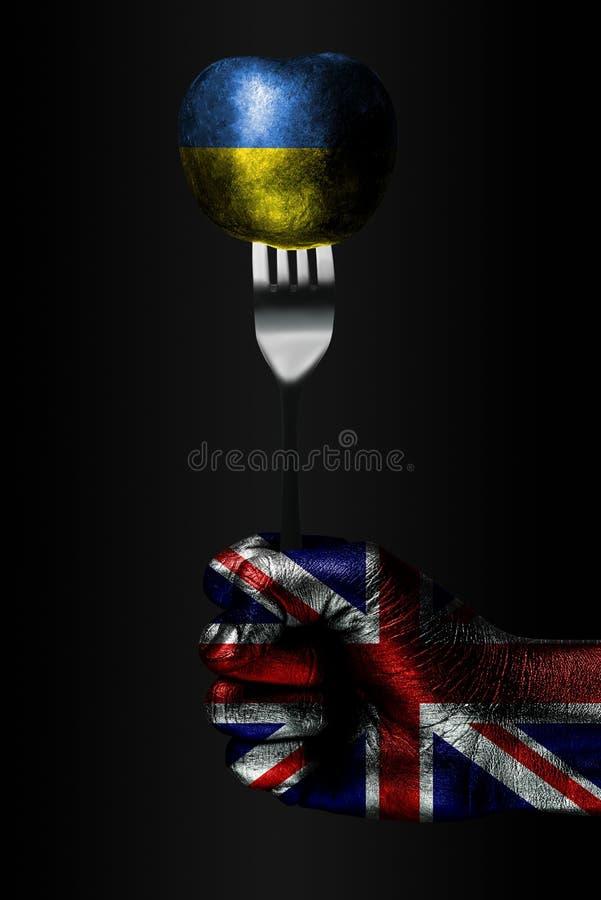 Рука с вычерченным флагом Великобритании держит вилку, на которой шарик с вычерченным флагом Украины, знак влияния, давления, стоковое изображение rf