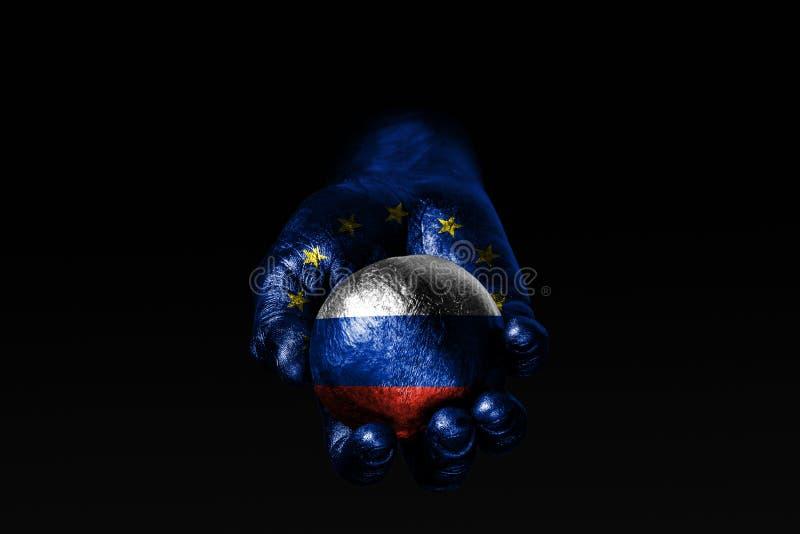 Рука с вычерченным флагом ЕС держит шарик с вычерченным флагом России, знак влияния, давление или консервацию и защиту стоковое изображение rf