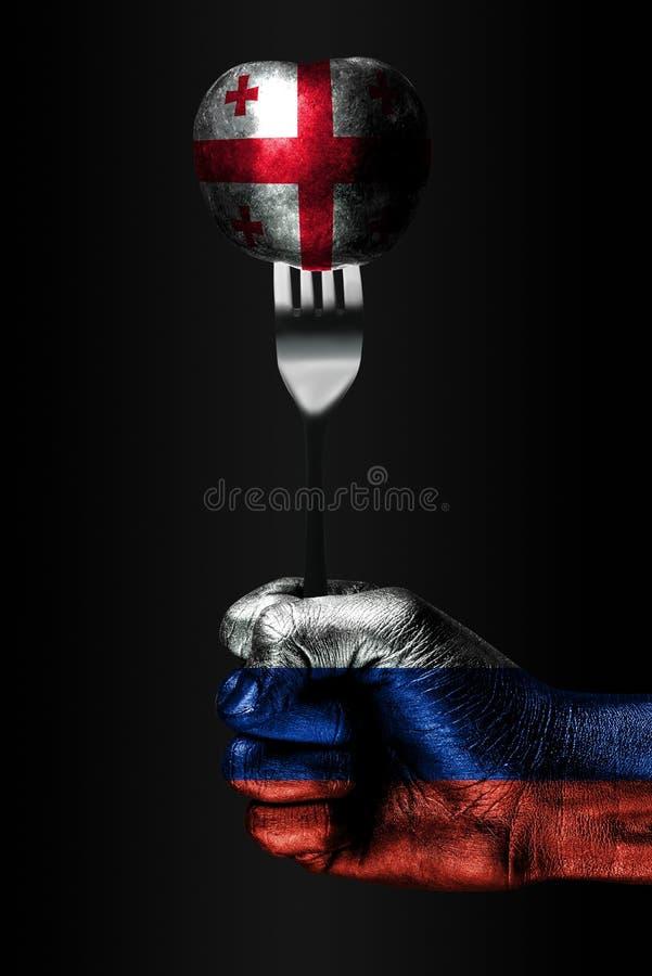 Рука с вычерченным флагом России держит вилку, на которой шарик с вычерченным флагом Грузии, знак влияния, давления, сжатия стоковые изображения rf
