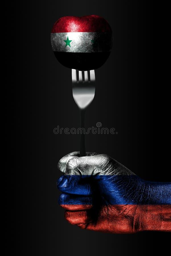 Рука с вычерченным флагом России держит вилку, на которой шарик с вычерченным флагом Сирии, знаком влияния, давления, сжатия и стоковое фото rf