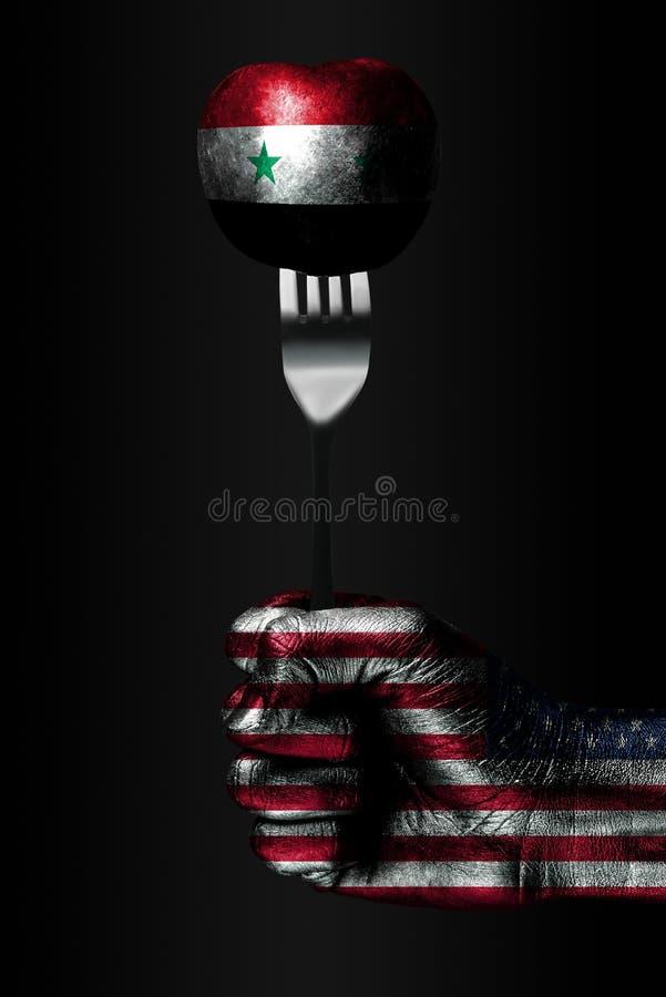 Рука с вычерченным флагом США держит вилку, на которой шарик с вычерченным флагом Сирии, знаком влияния, давления, сжатия и стоковая фотография