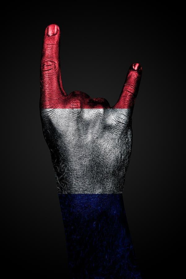 Рука с вычерченным флагом Франции показывает знак козы на темной предпосылке стоковая фотография rf