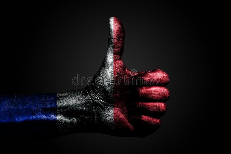 Рука с вычерченным флагом Франции показывает палец вверх по знаку, символ успеха, готовности, задачи сделанной на темной предпосы стоковая фотография