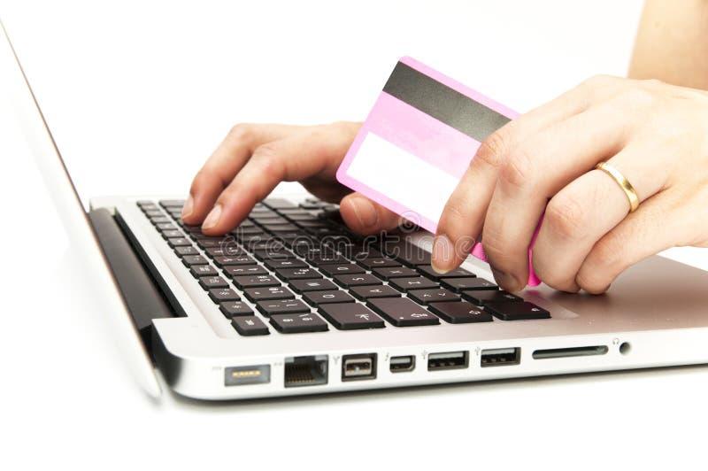 Рука с компьютером и кредитной карточкой стоковое изображение