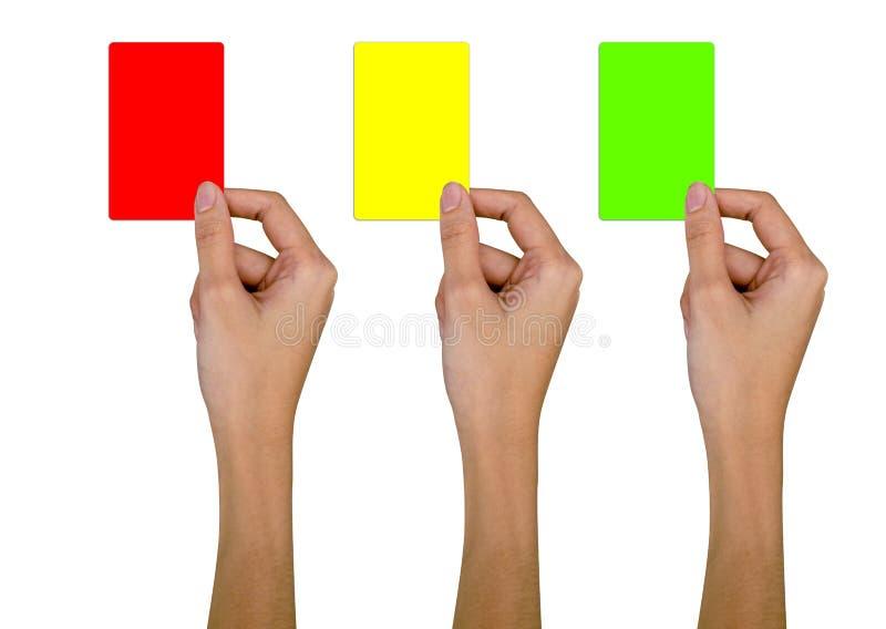 Рука с красной карточкой, желтой карточкой, зеленой карточкой на белом фоне стоковое изображение