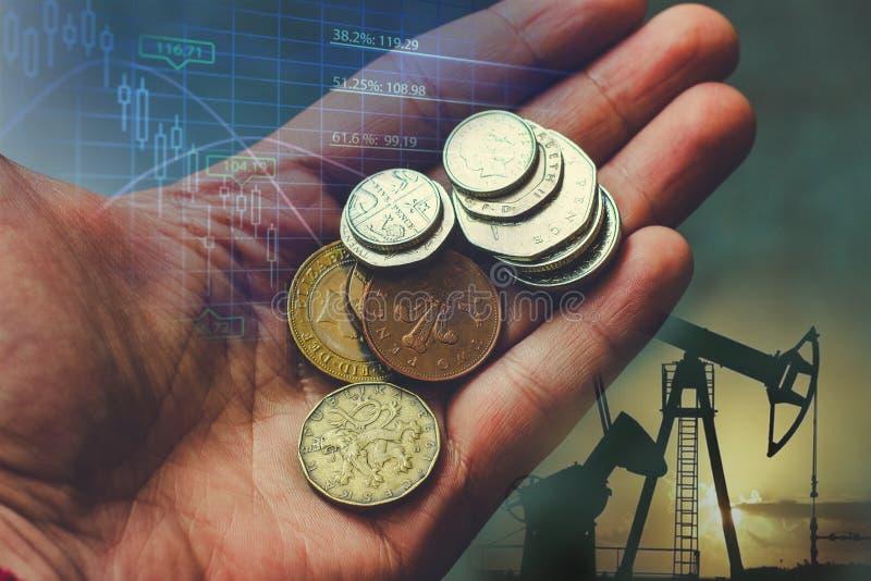 Рука с монетками на предпосылке добычи нефти Концепция дела, извлечение природных ресурсов стоковое фото rf