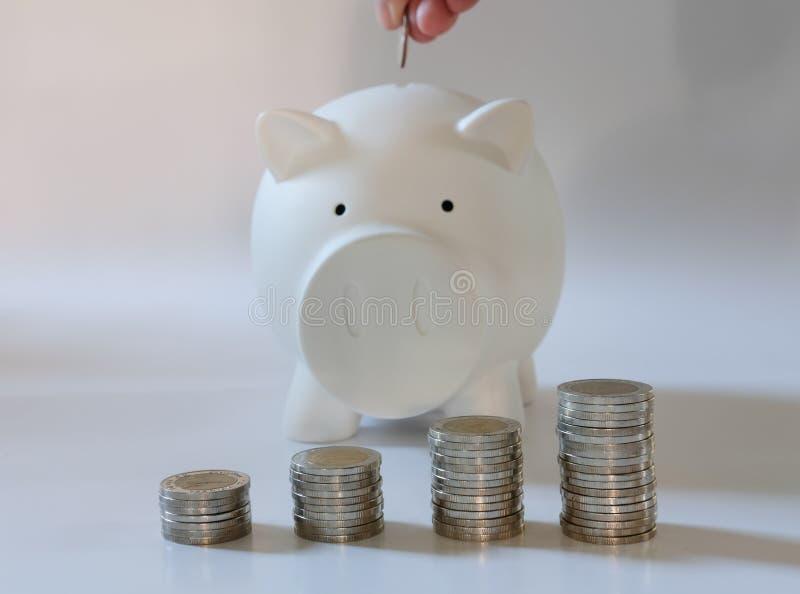 рука с монеткой над копилкой сбережения денег, депозит наличных денег conc стоковые изображения