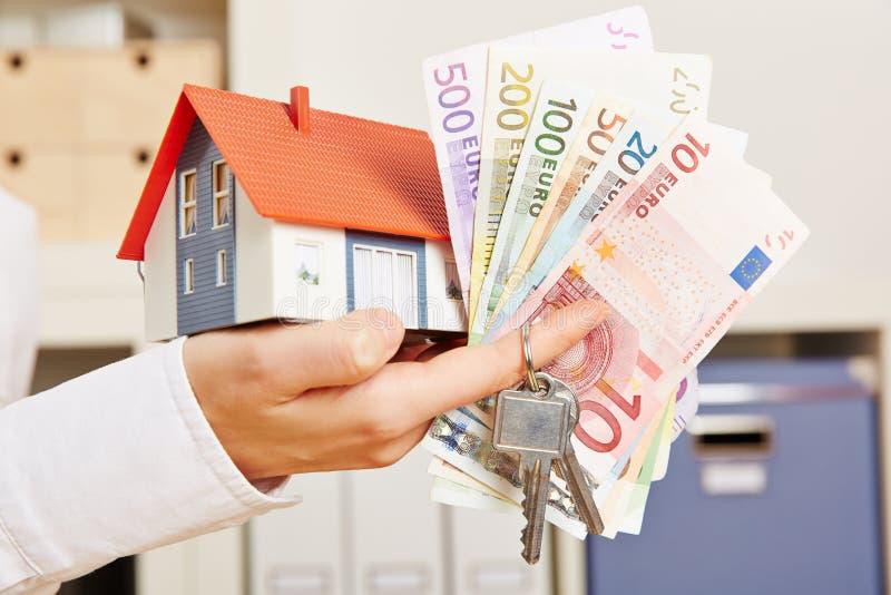 Рука с домом и деньгами и ключами стоковые изображения