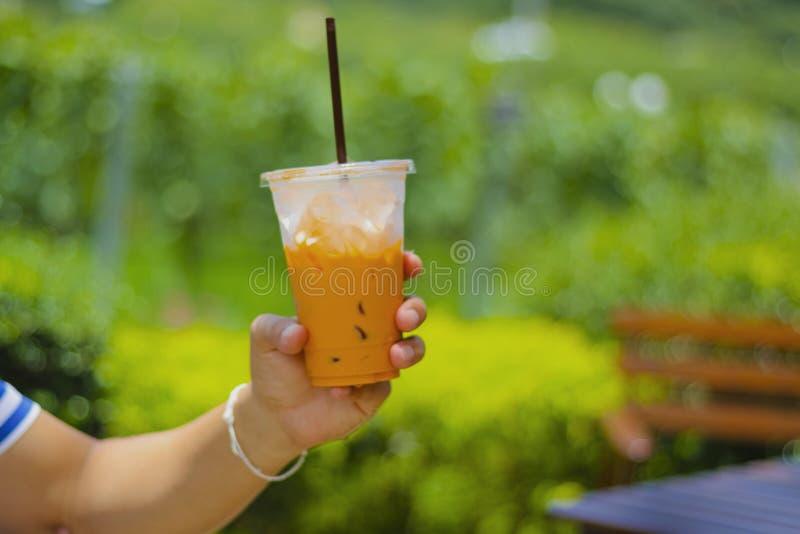 Рука с пластичным стеклом чая со льдом на таблице стоковое фото rf