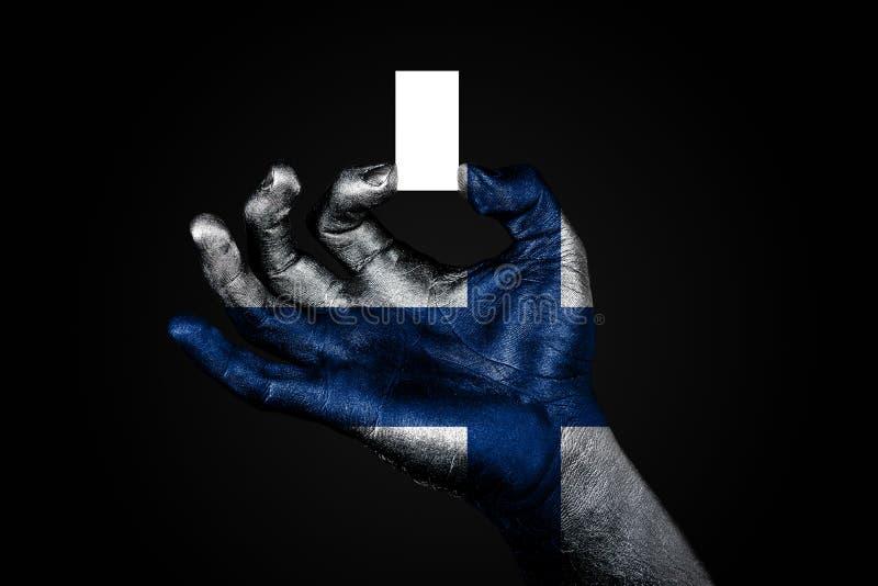 Рука с покрашенным флагом Финляндией держа небольшой белый лист с космосом для надписи, насмешливым вверх стоковые изображения