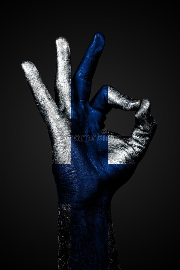 Рука с покрашенным флагом Финляндии показывает знак ОК на темной предпосылке стоковая фотография rf