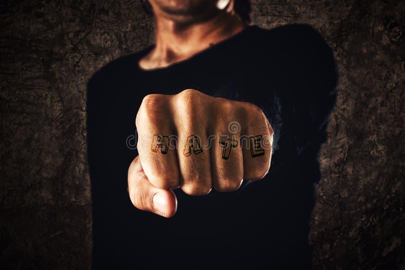 Рука с сжатым кулаком - татуированная ненависть стоковое фото rf