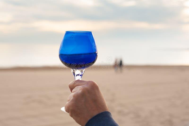 Рука с синим стеклом и пары целуя на пляже стоковое изображение