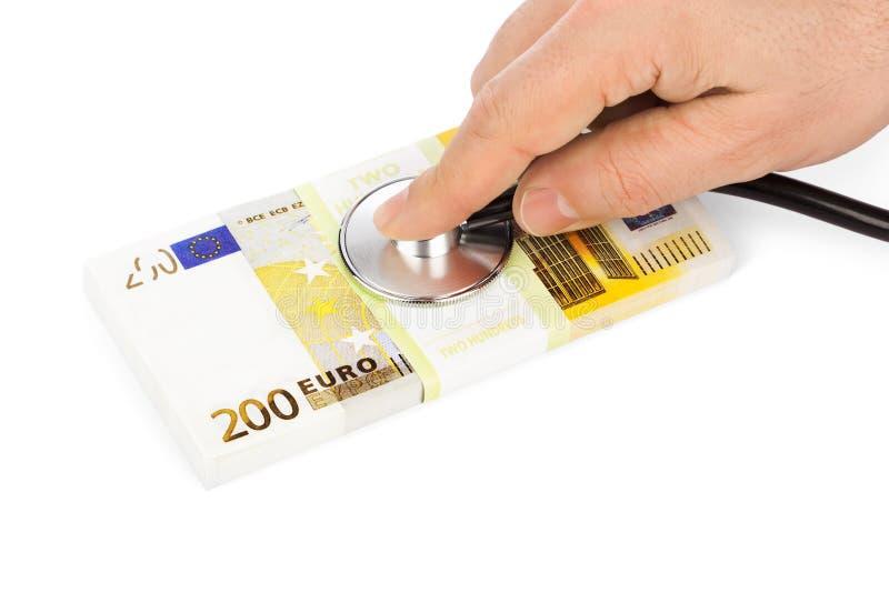 Рука с стетоскопом и деньгами стоковое изображение