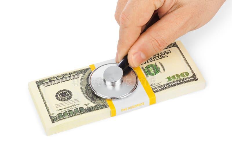 Рука с стетоскопом и деньгами стоковое фото rf