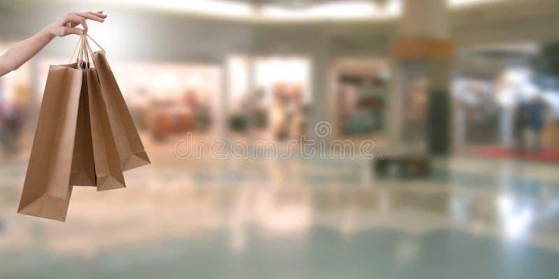 Рука с сумками и shooping центром стоковая фотография rf