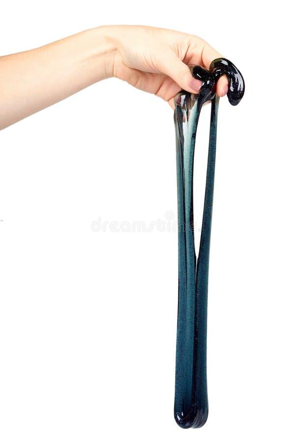 Рука с черной игрушкой шлама для детей, ярких блесков и липкой жидкости стоковое изображение