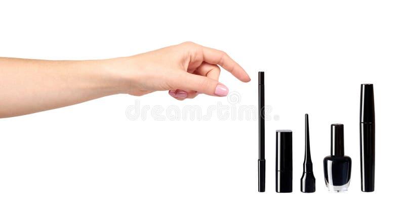 Рука с черными тушью, маникюром и губной помадой, щеткой макияжа глаза иллюстрация штока