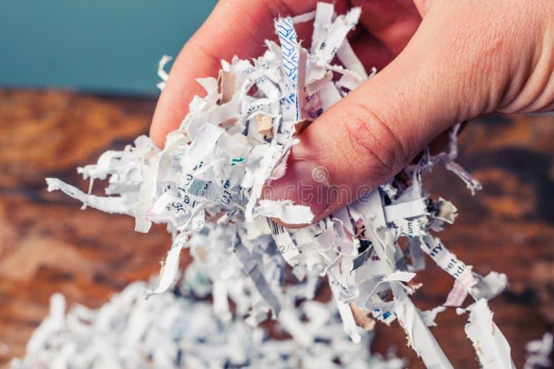 Рука с shredded бумагой стоковая фотография