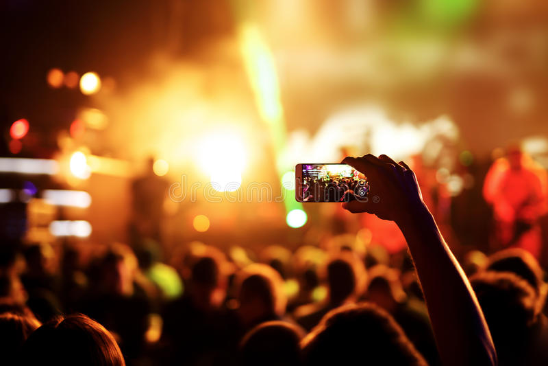 Рука с smartphone записывает фестиваль живой музыки, концерт в реальном маштабе времени, выставку на этапе стоковое изображение rf