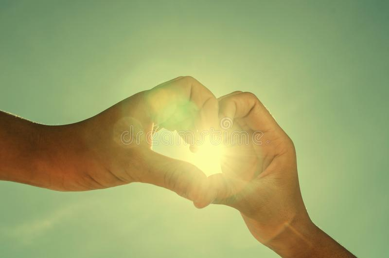 рука 2 формируя сердце сформировала с пирофакелом солнечного света и re года сбора винограда стоковые изображения
