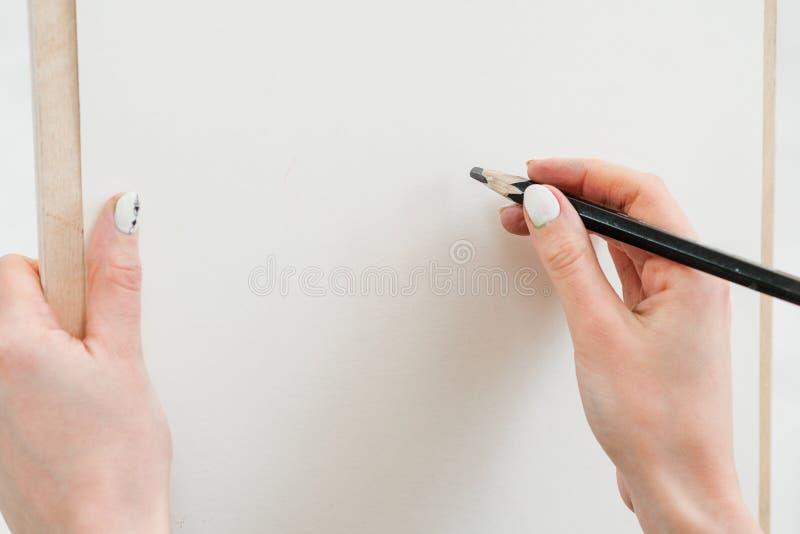 Рука художника женщины с большим простым карандашем, рисует на чистом белом холсте, конце-вверх стоковое изображение rf