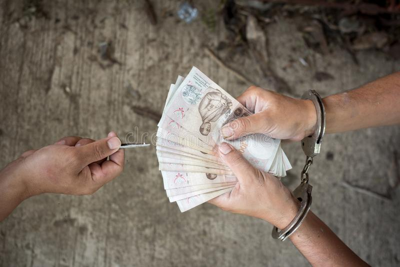 Рука человека в наручниках давая взятку, стоковое изображение