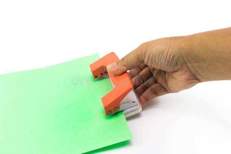 Рука человека делает используя оранжевый бумажный пунш с isola зеленой книги стоковое фото