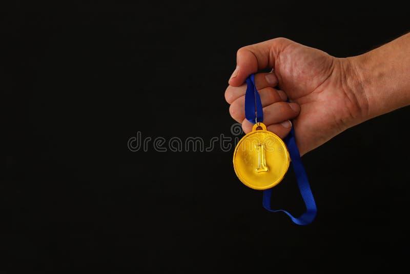 Рука человека держа золотую медаль против черной предпосылки концепция награды и победы стоковые изображения