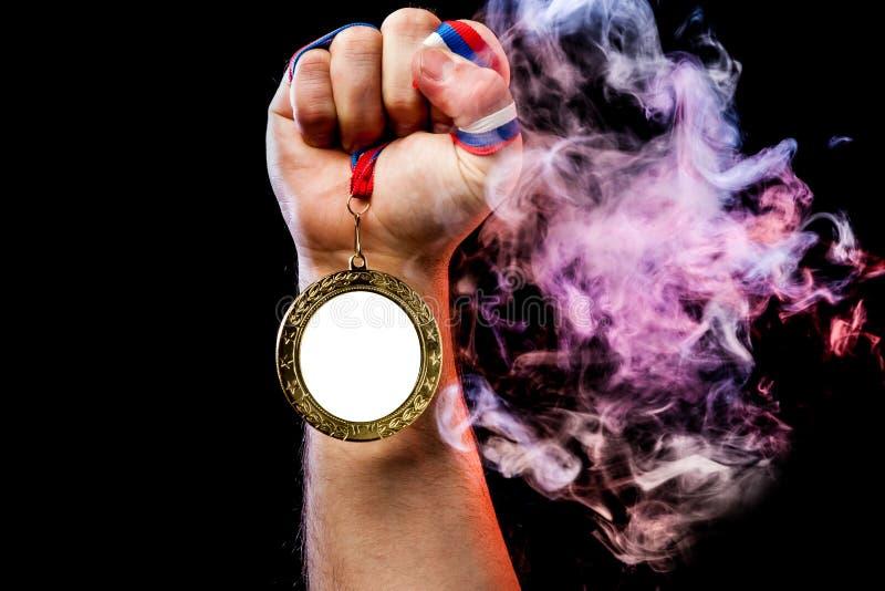 Рука человека держа золотую медаль стоковое изображение rf