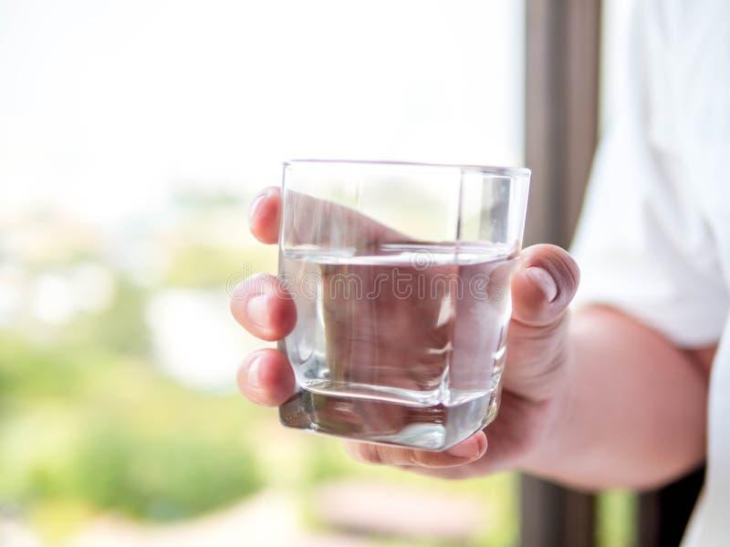 Рука человека держа ясное стекло воды для выпивать в утре стоковое изображение rf