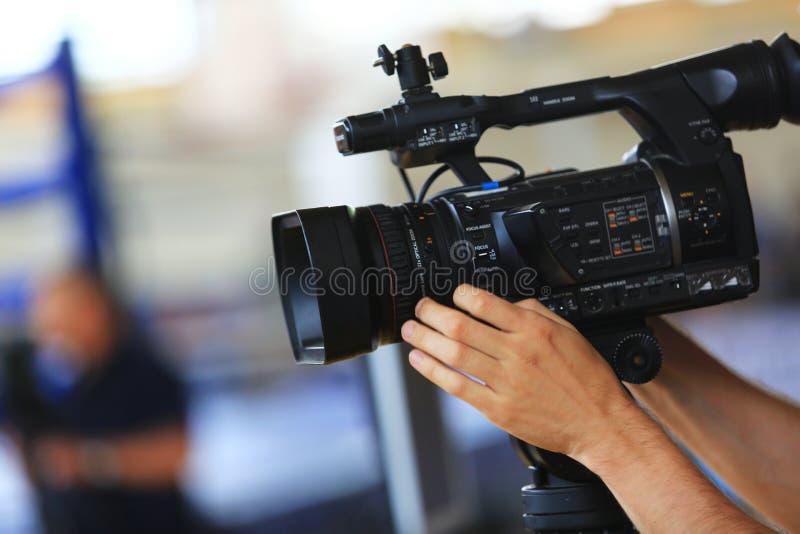 Рука человека держит цифровую черную видеокамеру стоковое изображение