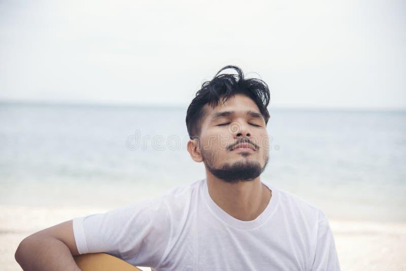 Рука человека играя гитару на пляже Акустический музыкант играя классическую гитару Музыкальная концепция стоковая фотография rf