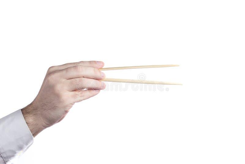 Рука человека используя палочки изолированные на белой предпосылке стоковое фото
