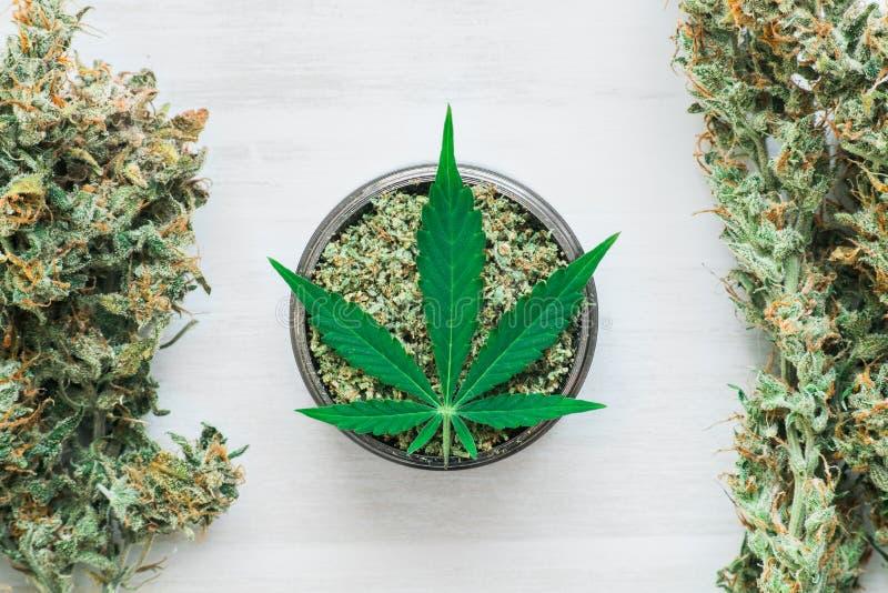 Рука человека свернула совместные бутоны марихуаны, развернутого засорителя на белом конце взгляд сверху предпосылки стоковые изображения