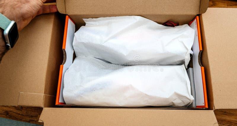 Рука человека unboxing распаковывающ новые e-покупки ботинок бега Nike стоковое фото