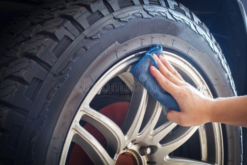 Рука человека держа автошины и колеса автомобиля чистки ткани сини стоковая фотография rf