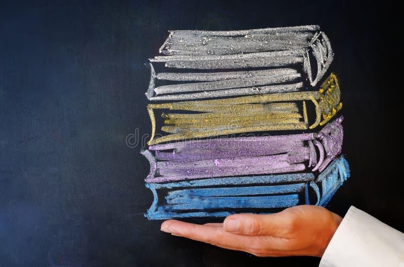 Рука человека держа стог книг нарисованных с мелом стоковое изображение