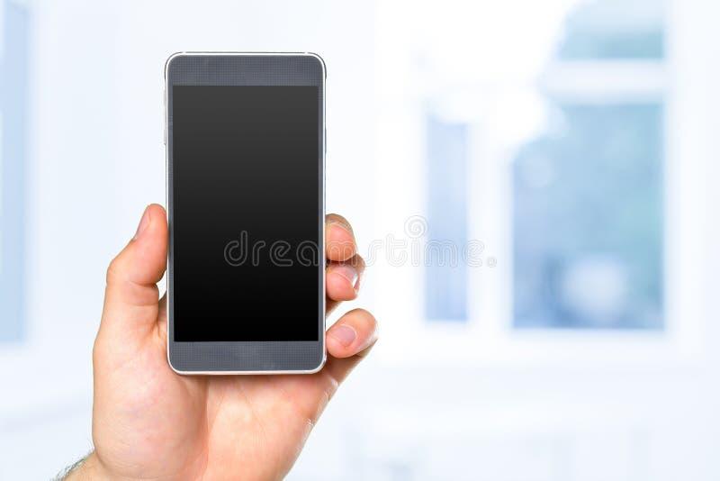 Рука человека держа smartphone стоковая фотография