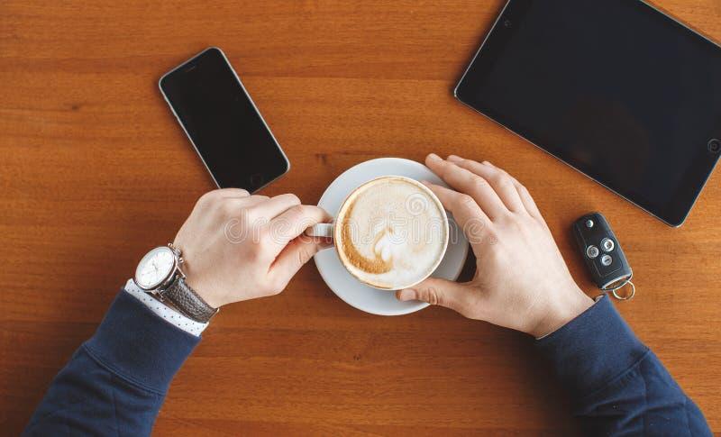 Рука человека, ключи чашки кофе, таблетки и автомобиля стоковые фотографии rf