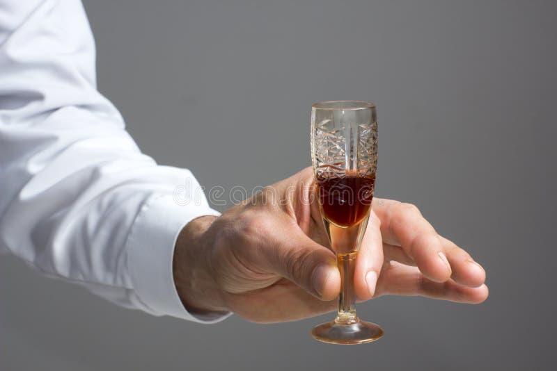 Рука человека на стекле аперитива стоковая фотография