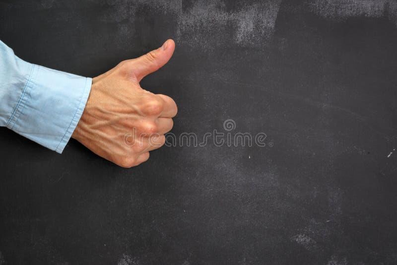 Рука человека показывать на темной доске с экземпляр-космосом стоковая фотография rf