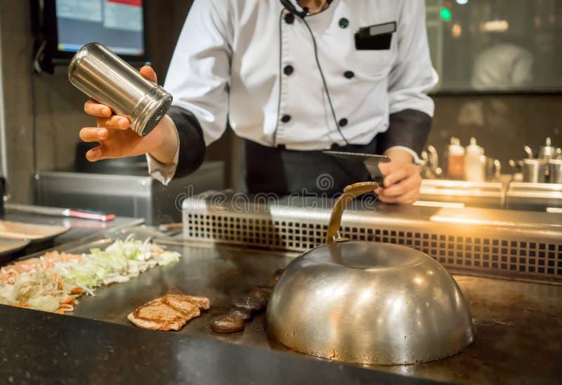Рука шеф-повара добавляя соль в стейк на горячем лотке перед c стоковые фотографии rf