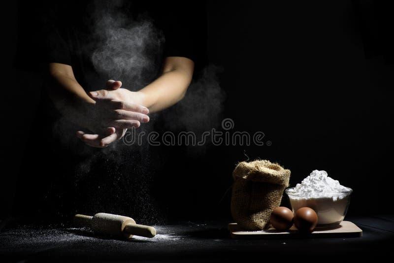 Рука шеф-повара молотит муки с деревянными вращающей осью и ингридиентами стоковая фотография rf