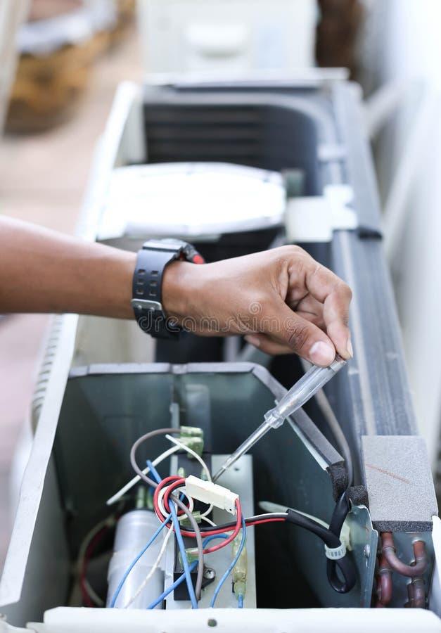 Рука электрика держа детектор на электрическом стоковые фотографии rf